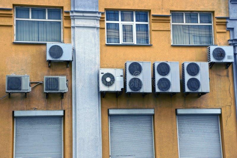 Airconditioners op de muur met vensters en deuren stock fotografie