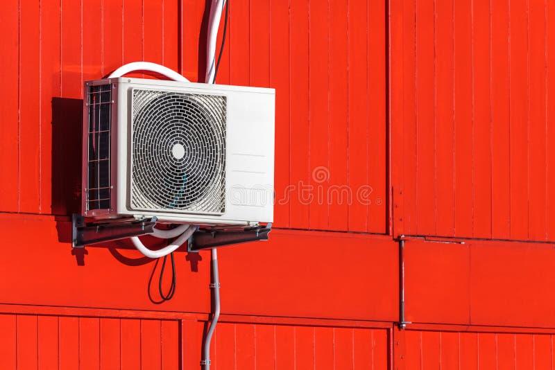 Airconditioningenhet på en röd vägg fotografering för bildbyråer