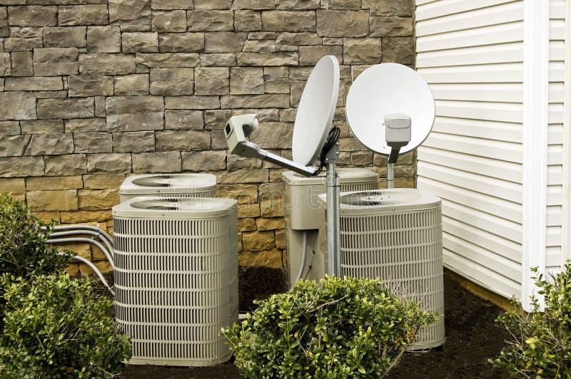 Airconditioningseenheden en Satellietschotels stock foto's