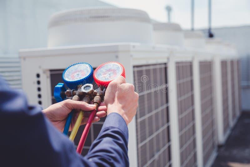Airconditioningstechnicus en a-een deel van het voorbereidingen treffen om nieuwe airconditioner te installeren stock afbeelding