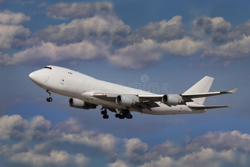 Boeing 747 Jumbo jet. White plane (boeing 747 jumbo jet) in the blue sky with clouds royalty free stock photography