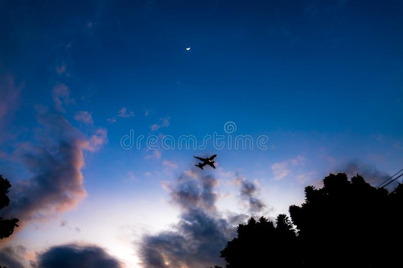 Aircraft on blue sky in night. Commercial aircraft on blue sky in night with crescent moon stock image