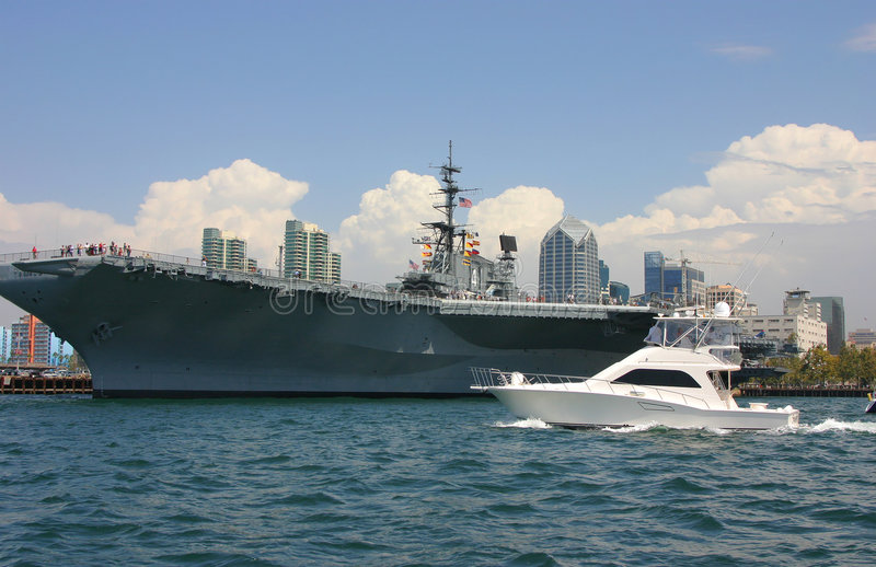 Aircraft Carrier and Yacht. In San Diego Bay stock photos