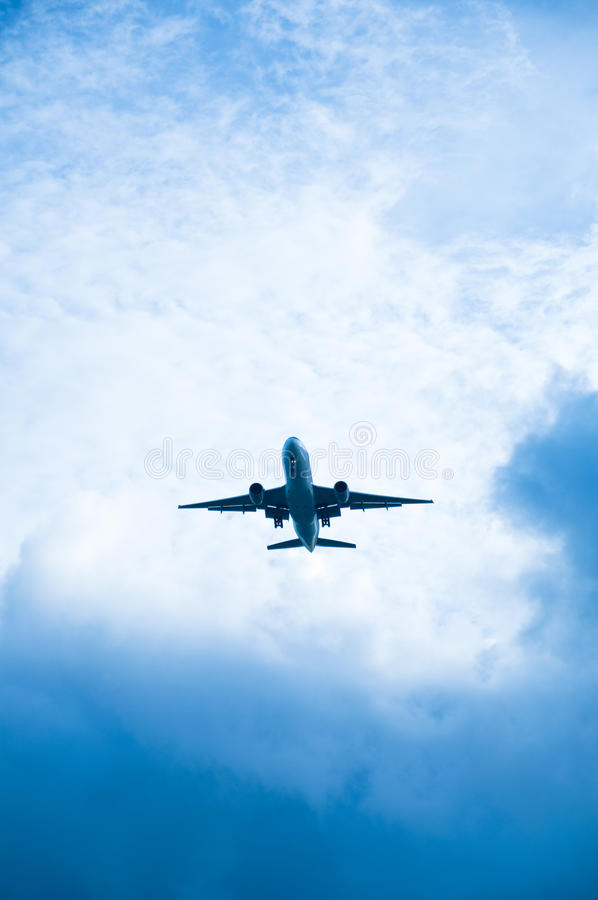 Aircraft in a clouded sky. A descending aircraft with cloud background royalty free stock photo