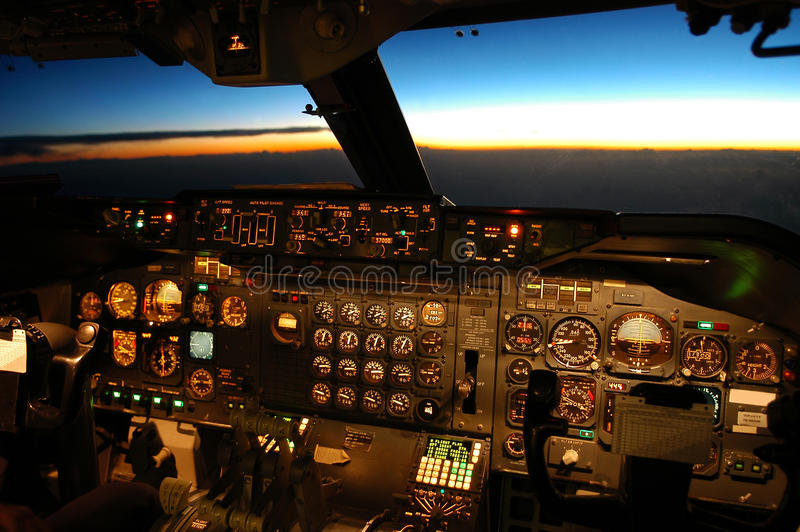 Aircraft cockpit. Boeing 747 cockpit view while flying west during sunset stock photos