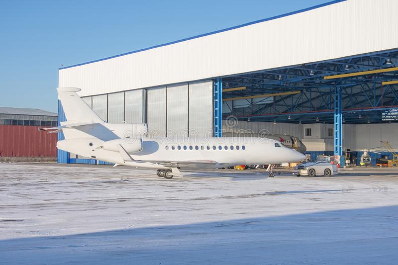 Aircraft is delivered inside via tow-tractor the aviation hangar for maintenance stock image