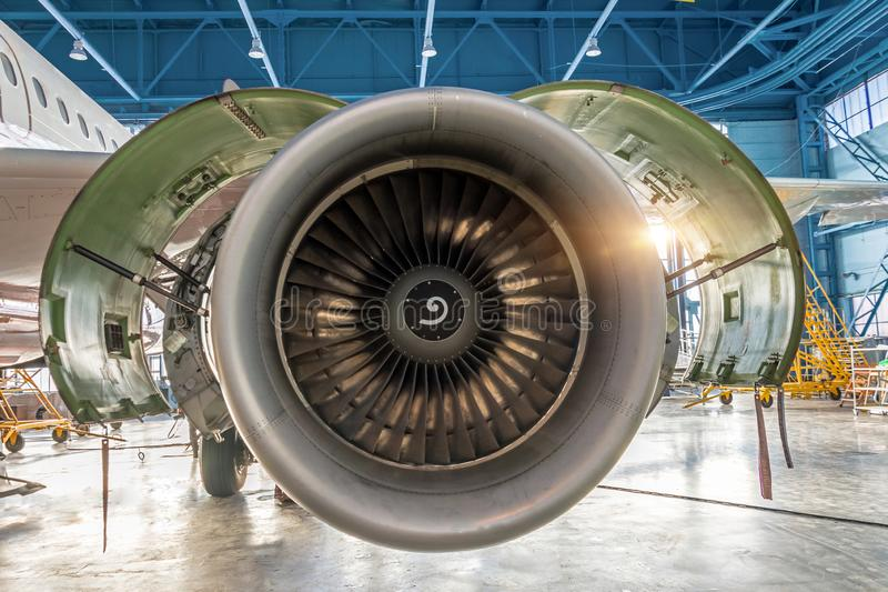 Aircraft engine jet with open hood on the sides in the hangar for maintenance stock image