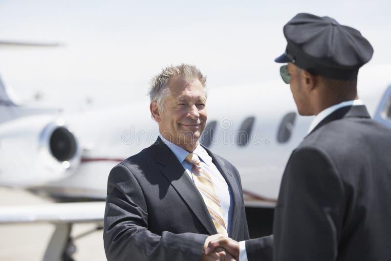 And Aircraft In för affärsmanShaking Hands With pilot bakgrund royaltyfri bild