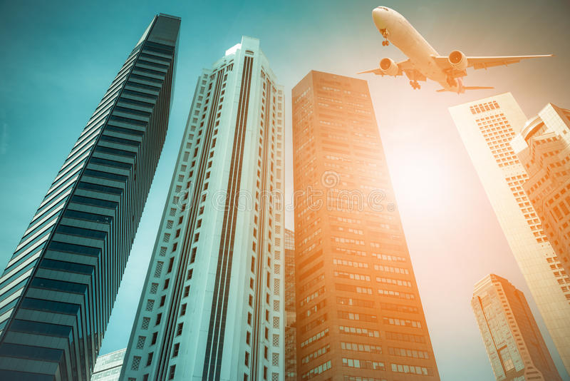 Aircraft flying over the modern city buildings in Singapore. stock photo