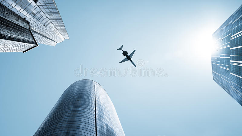 Aircraft flying over skyscrapers. Underside view of aircraft flying over skyscrapers in city stock images