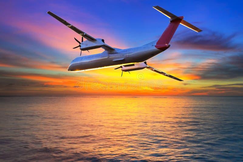 Aircraft Flying At Sunset Stock Photo