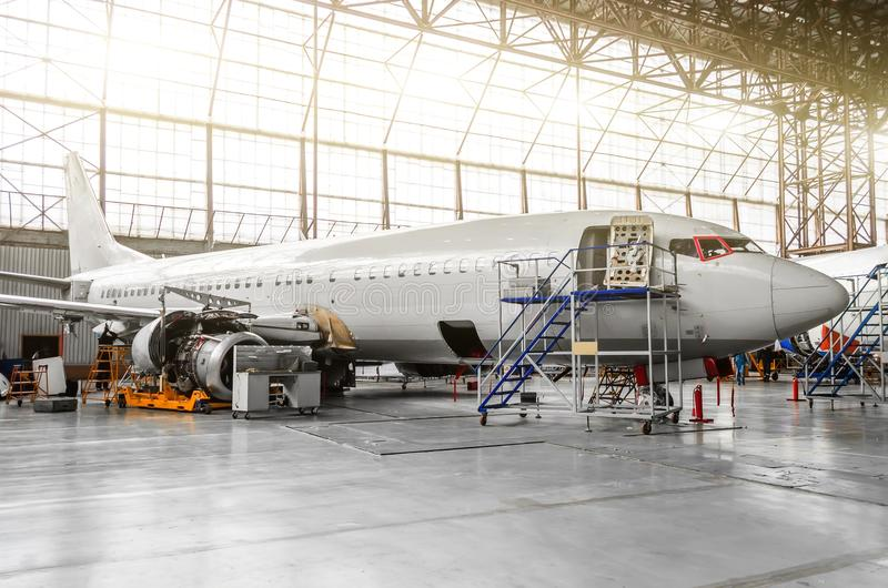 Aircraft in the hangar in the maintenance of plating, interior, engine repair. royalty free stock images