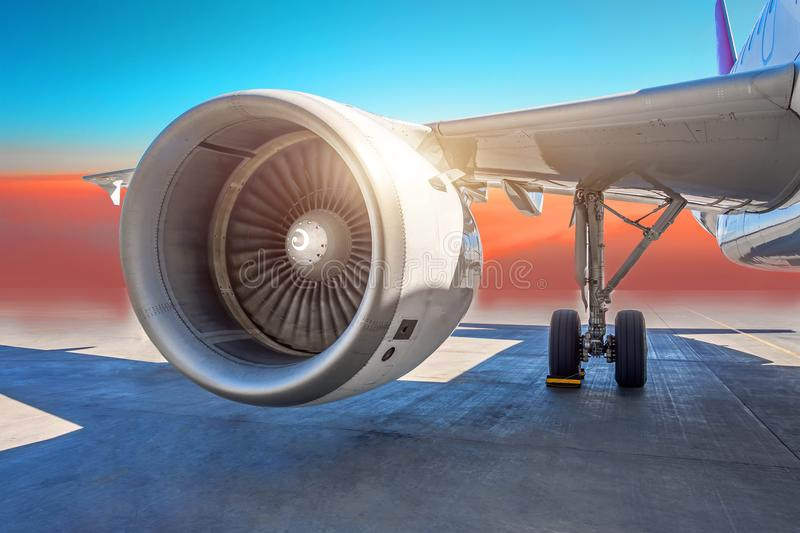 Aircraft jet engine close-up, airplane wing and chassis of landing gear wheel parked at the airport on a sky clouds background. Aircraft jet engine close-up stock images