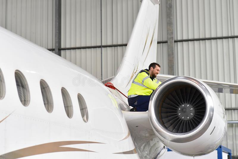 Aircraft mechanic inspects and checks the technology of a jet in a hangar at the airport. Closeup photo royalty free stock photo