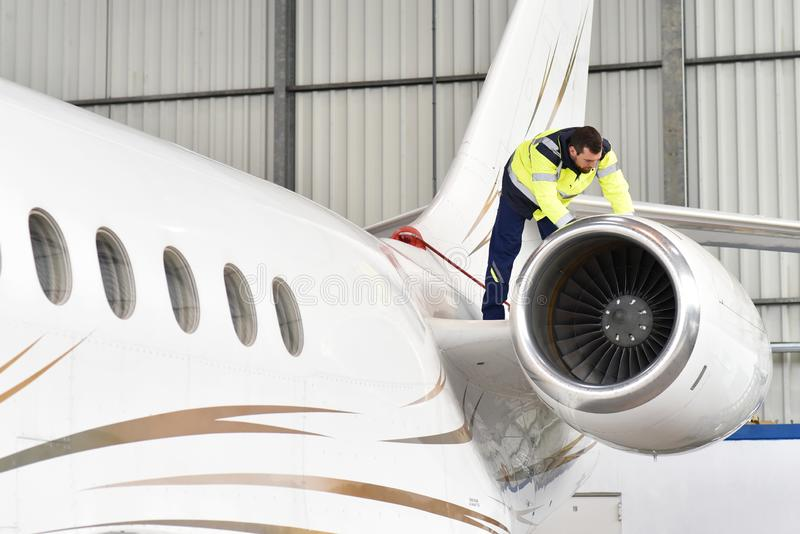 Aircraft mechanic inspects and checks the technology of a jet in a hangar at the airport. Closeup photo - closeup photo stock photos