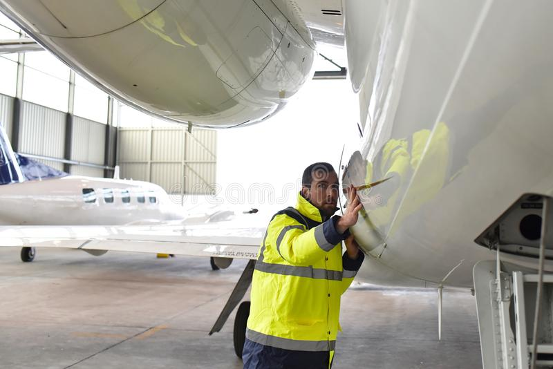 Aircraft mechanic inspects and checks the technology of a jet in a hangar at the airport. Closeup photo stock photography