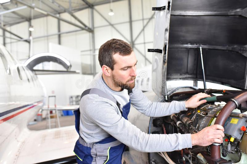 Aircraft mechanic repairs an aircraft engine in an airport hangar stock photos