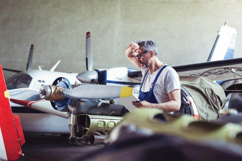 Aircraft mechanic repairs an aircraft engine in an airport hangar. Old Aircraft mechanic repairs an aircraft engine in an airport hangar royalty free stock photography