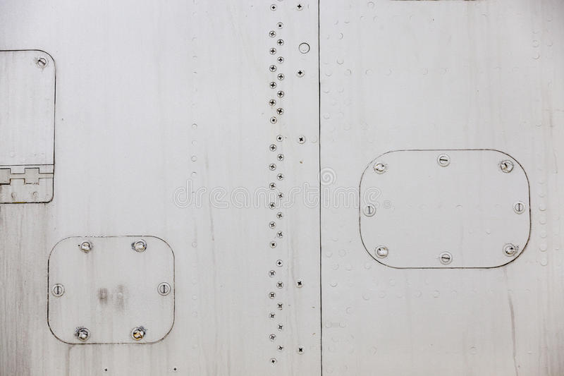 Aircraft metal cladding. Photographed close-up of metal siding military plane in gray, close-up, small depth of field royalty free stock photography