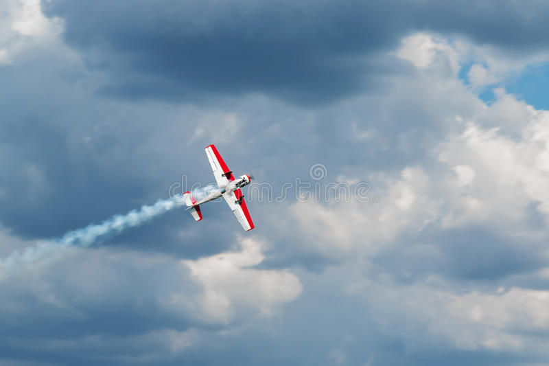 Aircraft produces fumes. Red - white plane jets of fumes in flight in a blue sky close-up royalty free stock image