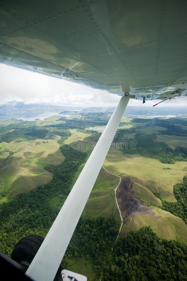 Aircraft Small. A small aircraft flies over Indonesian mountains stock photo