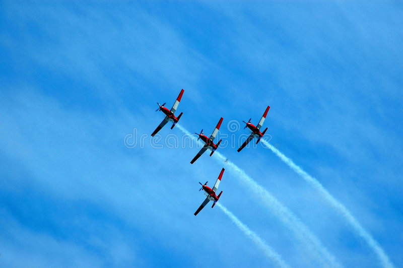 Aircraft teamwork. For small propeller airplanes in red and white on a flight show flying in the air showing teamwork royalty free stock photography