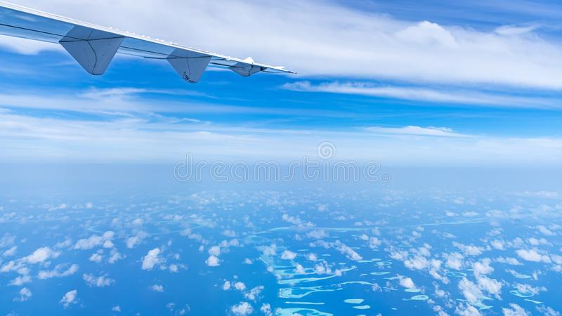 Aircraft wing flying over the blue clouds.  stock photos