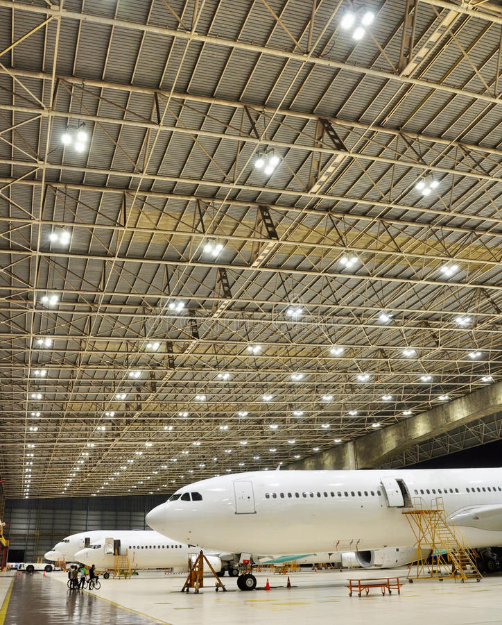 Aircrafts are parked in line at hangar, Soekarno Hatta Int Airport. 4 Aircraft were parked in line at hangar 2. The line of lamp bulbs enhance the beauty of this royalty free stock photo