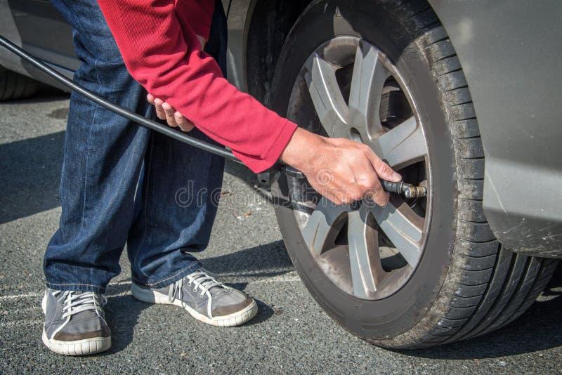 Aire de relleno del conductor en un neumático de un coche foto de archivo