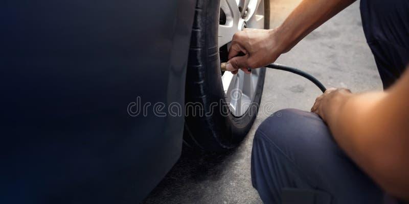 Aire de relleno del hombre en el neumático Conductor de coche Checking Air Pressure y mantenimiento su coche solo imagen de archivo