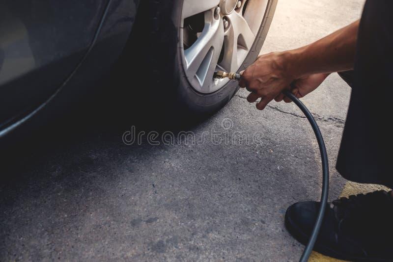 Aire de relleno del hombre en el neumático Conductor de coche Checking Air Pressure y mantenimiento su coche imagen de archivo