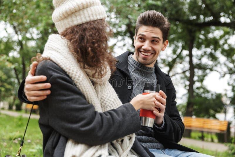 Aire libre de consumición del té o del café de los pares cariñosos jovenes felices en el parque que habla con uno a imagen de archivo libre de regalías