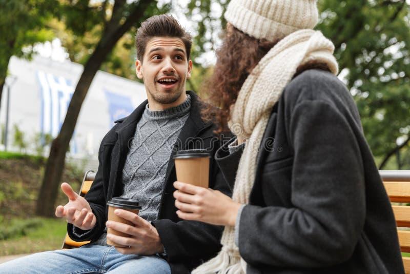 Aire libre de consumición del té o del café de los pares cariñosos jovenes felices en el parque que habla con uno a foto de archivo