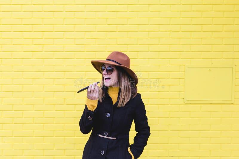 Aire libre de la mujer joven usando el teléfono móvil y el envío de un audio Forma de vida en la ciudad Amarillee el fondo de la  foto de archivo