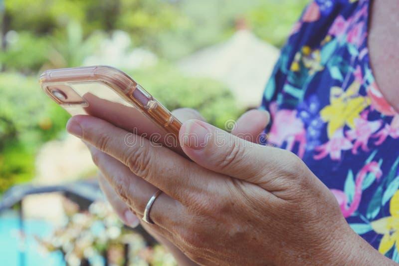 Aire libre de la mujer usando pantalla táctil del smartphone imagen de archivo libre de regalías