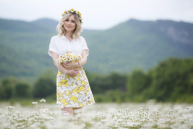 Aire libre hermoso de la mujer con un ramo de margaritas blancas en un prado floreciente de la montaña imagen de archivo