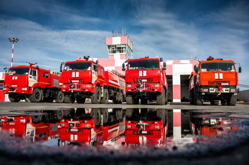 Airfield fire trucks with reflection in a puddle royalty free stock image