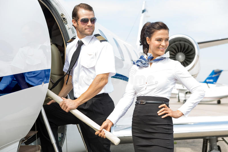 Airhostess med piloten Boarding Private Jet arkivbild