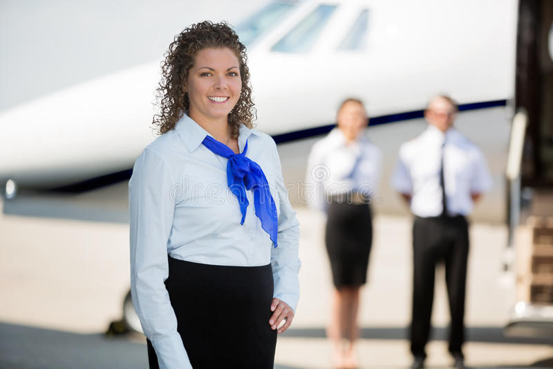 Airhostess ono Uśmiecha się Podczas gdy pilot I kolega fotografia stock