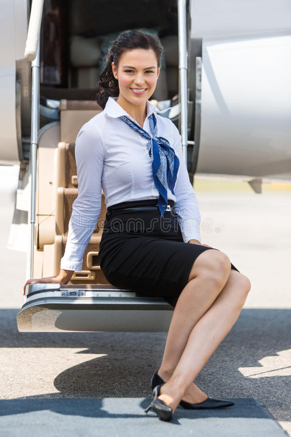 Airhostess Sitting On Ladder Of Private Jet stock photo