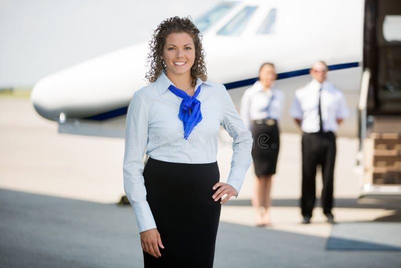 Airhostess Z ręką Na Modnej pozyci Przy lotniskiem zdjęcia stock