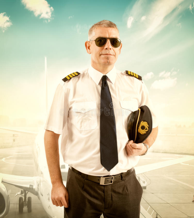 Airline pilot. Cheerful pilot wearing uniform with epaulettes, standing with airliner in background royalty free stock photo