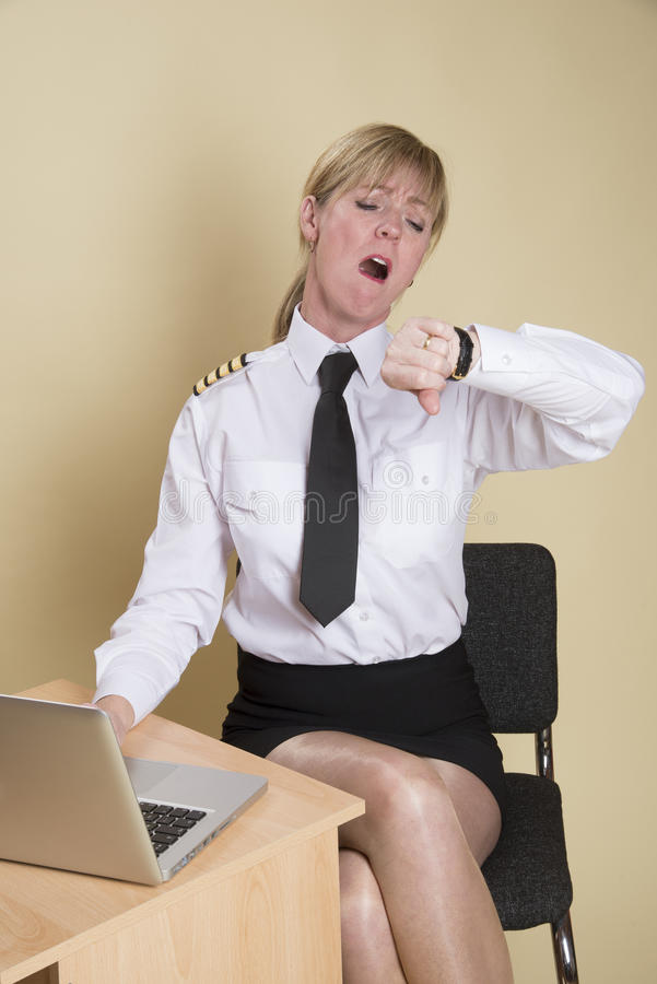 Airline pilot checking the time. Tired female airline pilot checking the time and wearing insignia of a captain royalty free stock photo