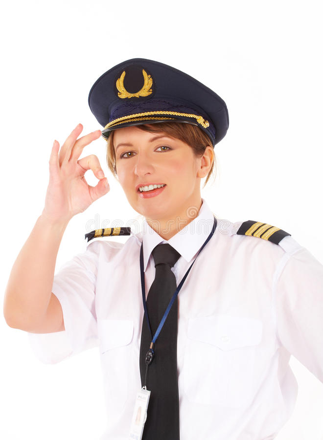 Airline pilot OK sign. Beautiful airline pilot wearing uniform with epaulets showing OK gesture of approval, standing isolated on white background royalty free stock photography