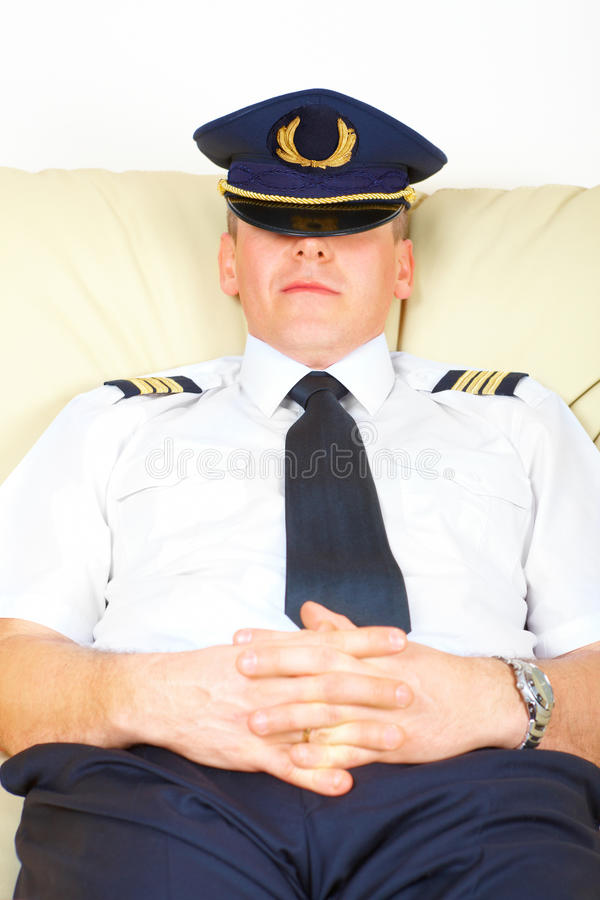 Airline pilot resting. Commercial pilot wearing uniform with epaulets and hat half sitting idly, resting or striking stock photography
