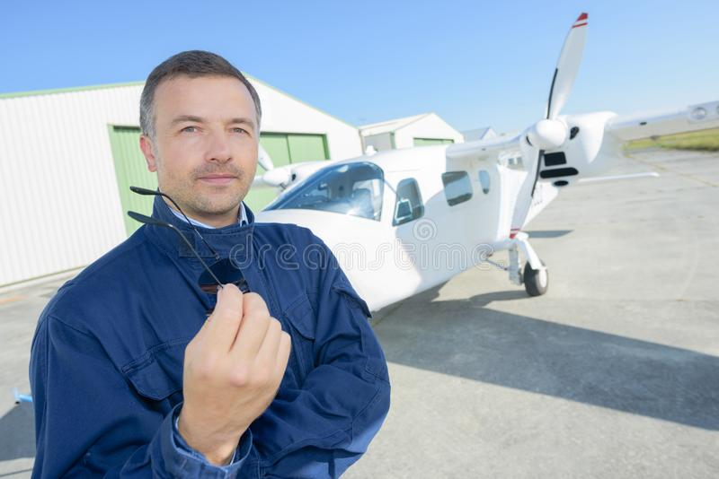 Airline pilot standing near aircraft royalty free stock image