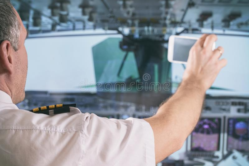 Airline pilot using smart phone stock photo