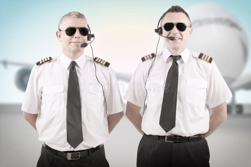 Airline pilots. Cheerful airline pilots wearing uniforms with epauletes and headsets standing with airliner in background stock image