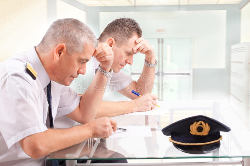 Airline pilots during exam. Two airline pilots during written exams could be used also as men filling papers before flight royalty free stock photography
