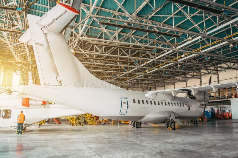 Airliner aircraft turboprop in a hangar with an open gate to the service. Airliner aircraft turboprop in a hangar with an open gate to the service stock photo